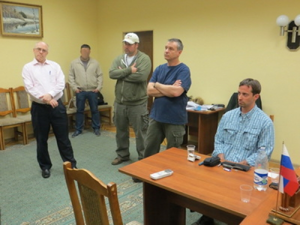 Райан Фогл за столом в приёмной ФСБ России вместе с прибывшими за ним представителями посольства США.